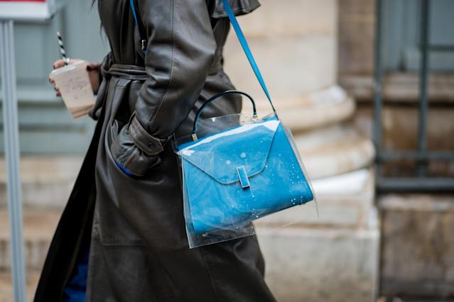 <p>Model carries Valextra Iside blue shoulder bag inside a clear plastic bag. (Photo: Getty Images) </p>