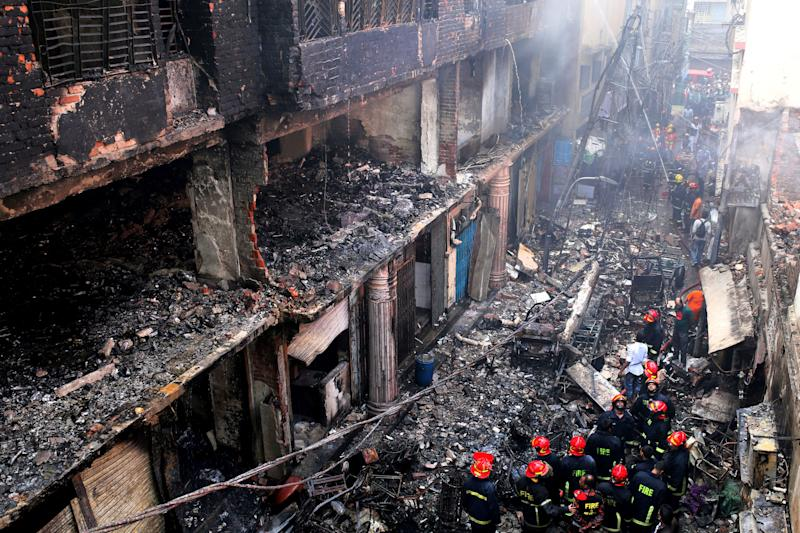 Locals and firefighters gather around buildings that caught fire late Wednesday in Dhaka, Bangladesh, Feb. 21, 2019. (Photo: Rehman Asad/AP)