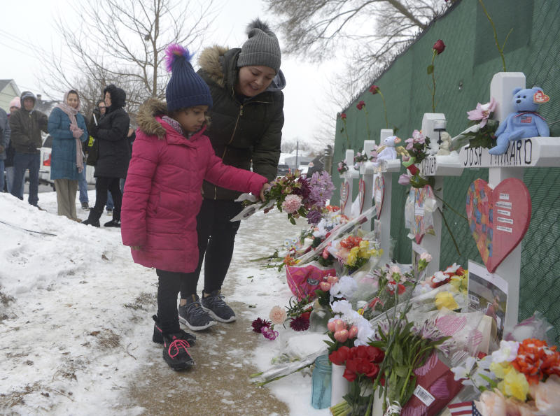 Mourners place a flower at the crosses outside of the Henry Pratt company in Aurora on Sunday, Feb. 17 in memory of the 5 employees killed on Friday.(Jeff Knox/Daily Herald via AP)