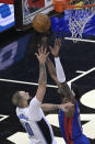 Orlando Magic guard Evan Fournier, left, is fouled by Detroit Pistons forward Jerami Grant, right, while going up for a shot during the first half of an NBA basketball game, Tuesday, Feb. 23, 2021, in Orlando, Fla. (AP Photo/Phelan M. Ebenhack)