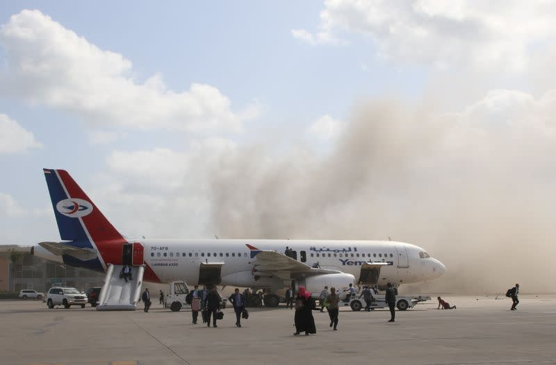 People walk on the tarmac as dust and smoke rise after explosions hit Aden airport, upon the arrival of the newly-formed Yemeni government in Aden
