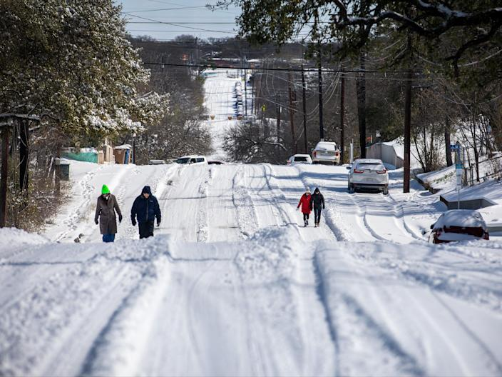 <p>Pedestrians walk on an icy road on 15 February 2021 in East Austin, Texas. Winter storm Uri has brought historic cold weather to Texas, causing traffic delays and power outages, and storms have swept across 26 states with a mix of freezing temperatures and precipitation</p> ((Getty Images))