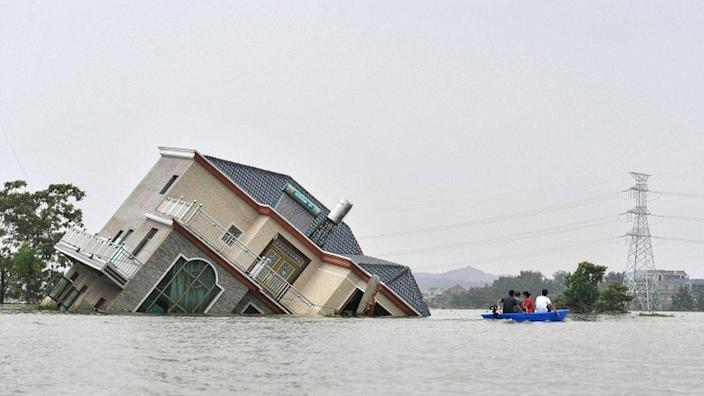This photo taken on 15 July 2020 shows residents riding a boat past a damaged and flood-affected house near the Poyang Lake due to torrential rains in Poyang county, Shangrao city in China's central Jiangxi province
