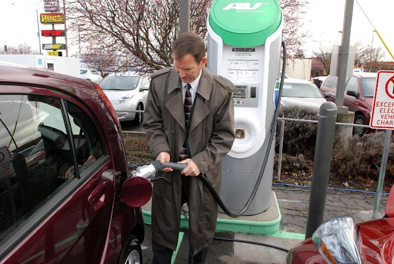 Thomas Miller, Western EV fleet sales manager for Mitsubishi Motors North America, demonstrates a fast-charger connection on a Mitsubichi i car Friday, March 16, 2012 in Central Point, Ore. Tucked in the back corner of a gas station off Interstate 5, this is one of eight new fast-charging stations that now allow electric cars to cruise from the California border to Eugene, Ore., recharging in about 20 minutes when the batteries get low. It is the first major section of what will eventually be an Electric Highway allowing electric cars to drive from Canada to Mexico on Interstate 5. (AP Photo/Jeff Barnard)