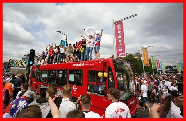 England fans standing on top of a bus