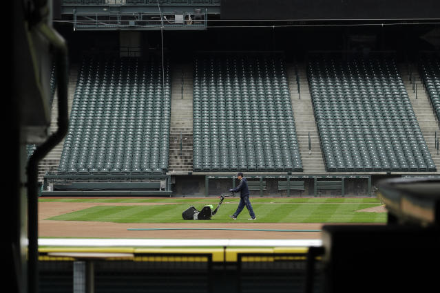 A grounds crew worker cuts the infield in front of empty seats at T-Mobile Park in Seattle, March 26, 2020, around the time when the first pitch would have been thrown in the Mariners' Opening Day baseball game against the visiting Texas Rangers. (AP Photo/Ted S. Warren)
