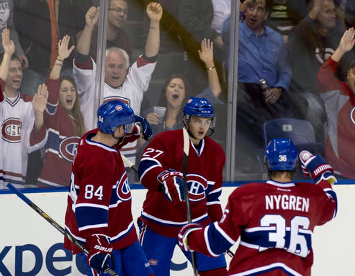 Montreal Canadiens' Alex Galchenyuk, center, is congratulated by teammates Darren Dietz, left, and Magnus Nygren after scoring against the Carolina Hurricanes during the first period of a preseason NHL hockey game Friday, Sept. 20, 2013, in Quebec City. (AP Photo/The Canadian Press, Jacques Boissinot)