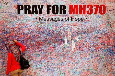 A woman leaves message of support and hope for passengers of missing Malaysia Airlines MH370 in central Kuala Lumpur