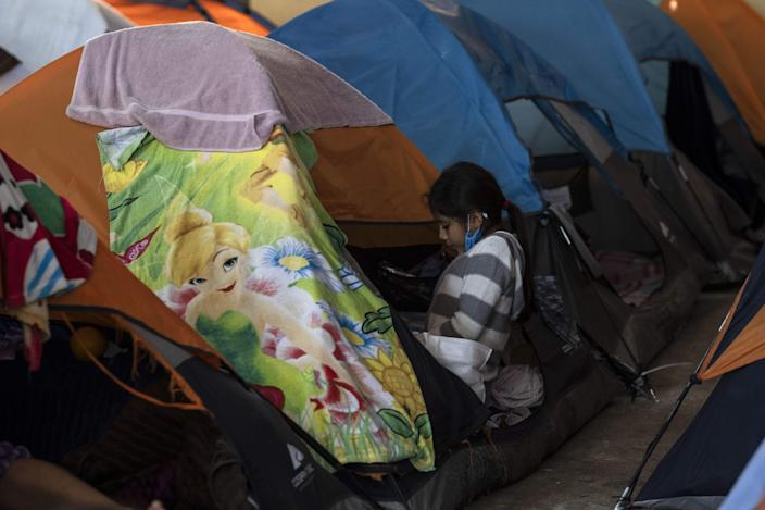 An asylum-seeker girl plays in her tent at the Juventud 2000 migrant shelter in Tijuana, Baja California State, Mexico, on April 3, 2020 during the novel coronavirus, COVID-19, pandemic. - Thousands of migrants overcrowding shelters or begging in the streets in Mexican cities along the US border are living in fear as the novel coronavirus spreads in the population and screening interviews for asylum seekers are being suspended. (Photo by Guillermo ARIAS / AFP) (Photo by GUILLERMO ARIAS/AFP via Getty Images)