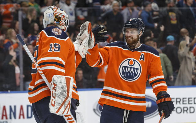 Edmonton Oilers' goalie Mikko Koskinen (19) and Adam Larsson (6) celebrate a 2-1 win over the Anaheim Ducks in an NHL hockey game Saturday, Feb. 23, 2019, in Edmonton, Alberta. (Jason Franson/The Canadian Press via AP)