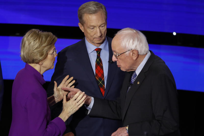 Democratic presidential candidate Sen. Elizabeth Warren, D-Mass., left and Sen. Bernie Sanders, I-Vt., talk Tuesday, Jan. 14, 2020, after a Democratic presidential primary debate hosted by CNN and the Des Moines Register in Des Moines, Iowa., as businessman Tom Steyer looks on. (AP Photo/Patrick Semansky)