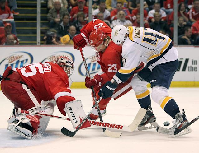 DETROIT, MI - APRIL 15: Jimmy Howard #35 of the Detroit Red Wings keeps an eye on the puck behind teammate Brad Stuart #23 and Alexander Radulov #47 of the Nashville Predators during Game Three of the Western Conference Quarterfinals during the 2012 NHL Stanley Cup Playoffs at Joe Louis Arena on April 15, 2012 in Detroit, Michigan. Nashville won the game 3-2 and lead the series 2-1. (Photo by Gregory Shamus/Getty Images)