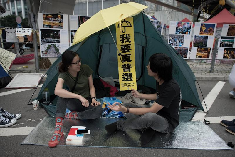 Pro-democracy protesters talk outside their tent in the Admiralty district of Hong Kong, on October 25, 2014 (AFP Photo/Nicolas Asfouri)
