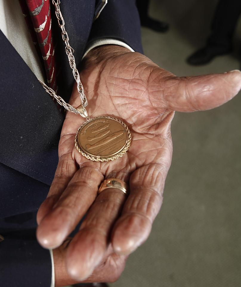 "In this Jan. 10, 2012 photo, Tuskegee airman Floyd Carter Sr. displays his medal during the ""Red Tails"" press junket in New York. ""Red Tails,"" a film that chronicles the heroism of the Tuskegee Airmen, opens Friday, Jan. 20. (AP Photo/Carlo Allegri)"