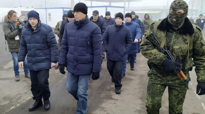 A Russia-backed separatist soldier escorts a group of separatists war prisoners after they were exchanged near the checkpoint Horlivka, eastern Ukraine, Sunday, Dec. 29, 2019. Ukrainian forces and Russia-backed rebels in the east have begun exchanging prisoners in a move aimed at ending their five-year-long war. (AP Photo/Alexei Alexandrov)