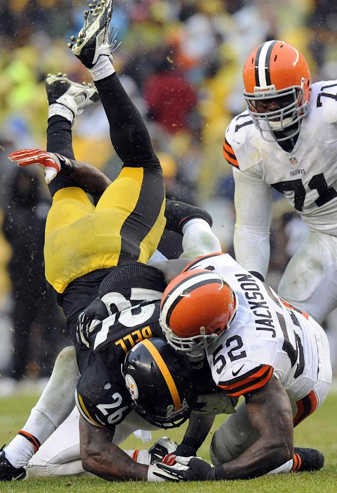Pittsburgh Steelers running back Le'Veon Bell (26) flips as he is hit by Cleveland Browns inside linebacker D'Qwell Jackson (52) in the second quarter of an NFL football game on Sunday, Dec. 29, 2013, in Pittsburgh. (AP Photo/Don Wright)