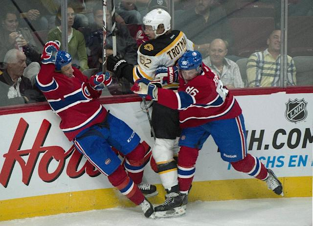 Boston Bruins' Zach Trotman, centre, collides with Montreal Canadiens' Ryan White, left, and Stefan Fournier during the third period of an NHL preseason hockey game in Montreal, Monday, Sept. 16, 2013. (AP Photo/The Canadian Press, Graham Hughes)