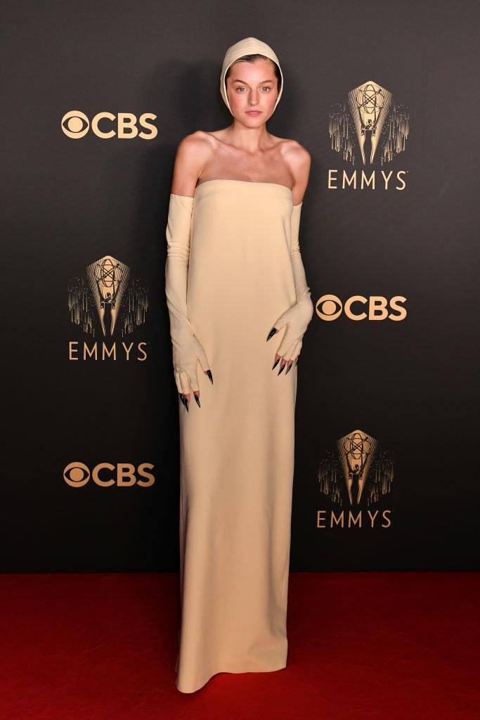 Emma Corrin on the red carpet in an all beige gown and matching bonnet