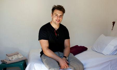 Co-founder and CEO of Airbnb Brian Chesky sits on a bed at a bed and breakfast in Langa township, Cape Town