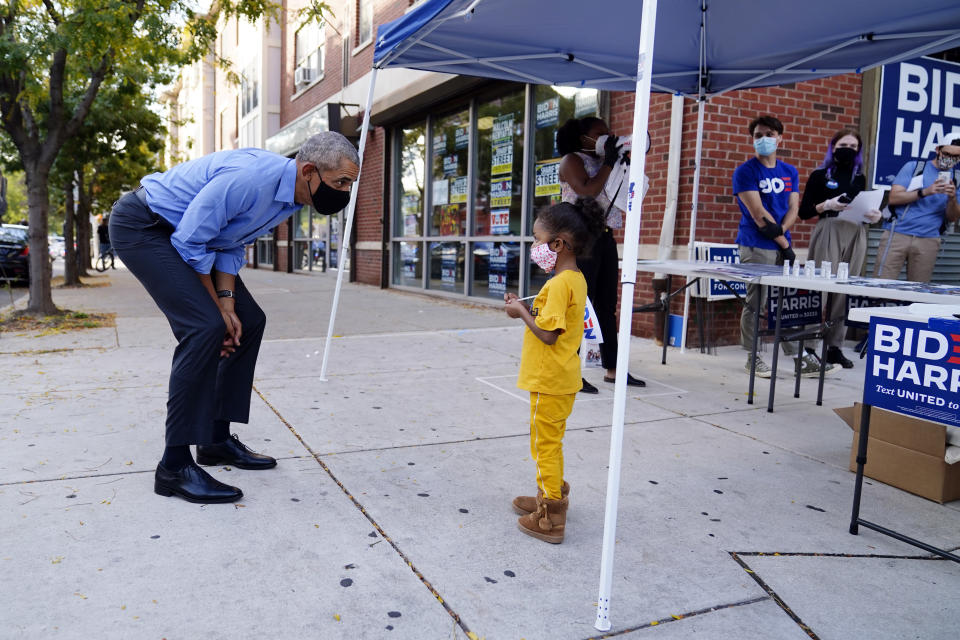 Former President Barack Obama speaks speaks to a child outside of a Democratic Voter Activation Center as he campaigns for Democratic presidential candidate former Vice President Joe Biden, Wednesday, Oct. 21, 2020. (AP Photo/ Matt Slocum)
