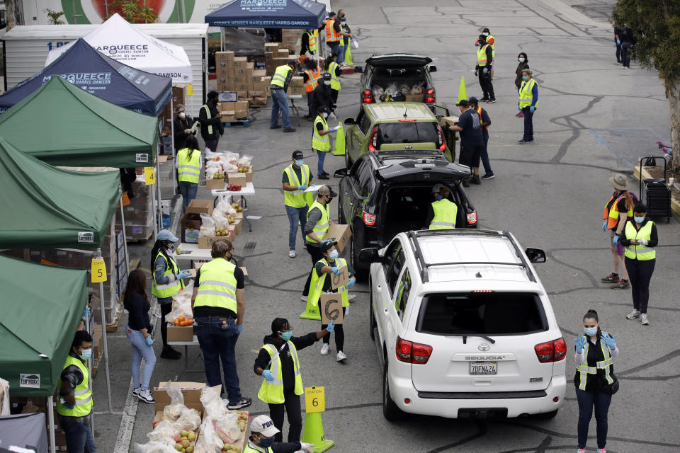 FILE — In this April 7, 2020 file photo food is loaded into vehicles at a food distribution center in the Crenshaw district of Los Angeles. Gov. Gavin Newsom suffered political backlash after it surfaced that he and his wife attended a party Nov. 6, 2020, with a dozen friends at the pricy French Laundry restaurant in wine country north of San Francisco. Newsom is facing the second recall of a governor in California history and the last day to vote is Sept. 14, 2021.AP Photo/Marcio Jose Sanchez,File)
