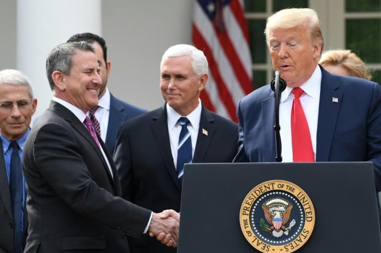 Donald Trump shakes hand with Brian Cornell, CEO of Target, at a White House event on preventing spread of the coronavirus