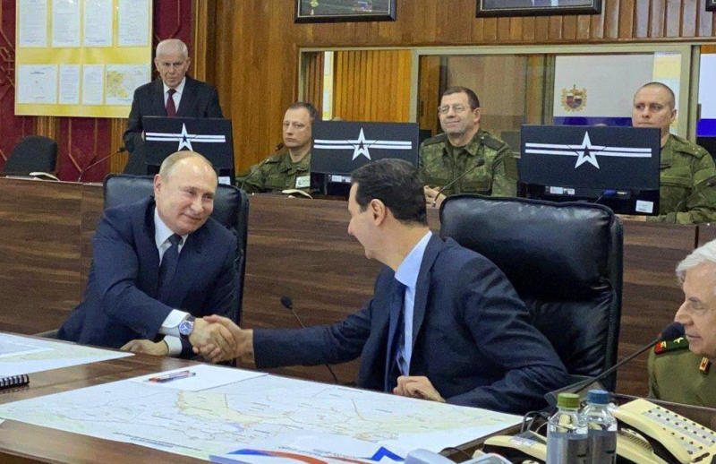 This image released by the Syrian Presidency shows Russian President Vladimir Putin, left, meeting with Syrian President Bashar Assad, center, in Damascus, Syria on Tuesday, Jan. 7, 2020. Putin's visit is the second to the war-torn country where his troops have been fighting alongside Syrian government forces since 2015. (Syrian Presidency via AP)