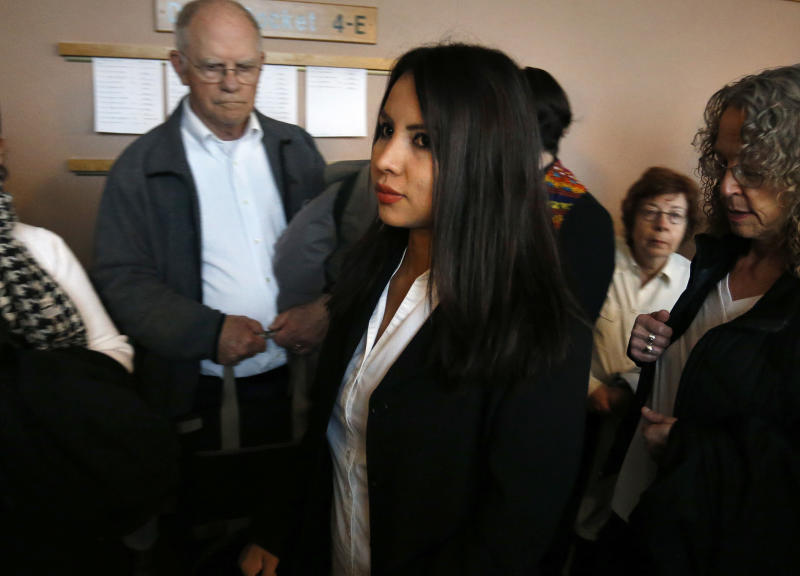 FILE - In a Wednesday, May 3, 2017 file photo, sanctuary church resident Ingrid Encalada Latorre, center, enters a courtroom inside the Jefferson County Courthouse, in Golden, Colo.  Latorre, mother of two children who sought sanctuary at a Quaker meeting house in Denver to avoid U.S. immigration authorities has been granted a temporary stay from deportation. Latorre, a 33-year-old native of Peru, and her attorney announced Saturday, May 20  that U.S. Immigration and Customs Enforcement officials agreed not to pursue deportation through Aug. 7.  (AP Photo/Brennan Linsley, File)