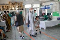 A child walks with his new prosthetic legs assisted by a relative at an International Committee of Red Cross Rehabilitation Centre in Kabul (AFP/BULENT KILIC)