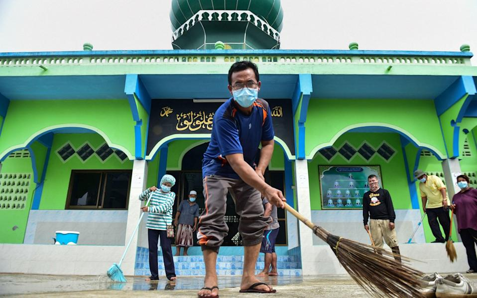 People clean the compound of a mosque in preparation for reopening, in Narathiwat, Thailand on June 13 2021 - Madaree Tohlala/AFP