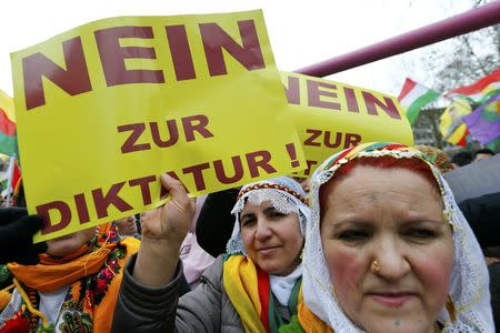 "People hold placards with the slogan ""No to dictatorship"" during a demonstration organised by Kurds, in Frankfurt, Germany, March 18, 2017.  REUTERS/Ralph Orlowski"