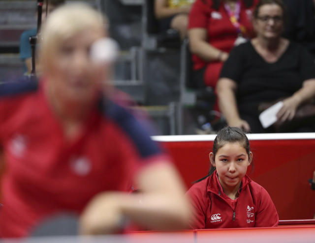Wales' eleven-year-old table tennis player Anna Hursey, right, watches teammate Charlotte Carey play against India's Manika Batra during their women's team match the 2018 Commonwealth Games at the Oxenford Studios on the Gold Coast, Australia, Thursday, April 5, 2018. (AP Photo/Rick Rycroft)
