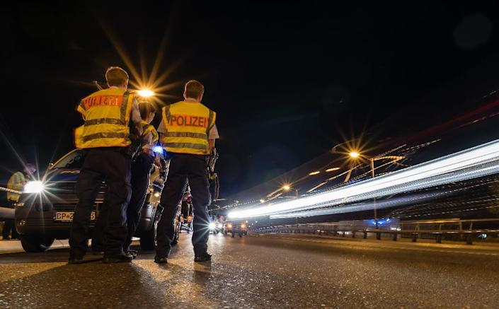 German police officers stand on the side of the road as they check cars on September 13, 2015, in the southern German city of Freilassing (AFP Photo/Guenter Schiffmann)