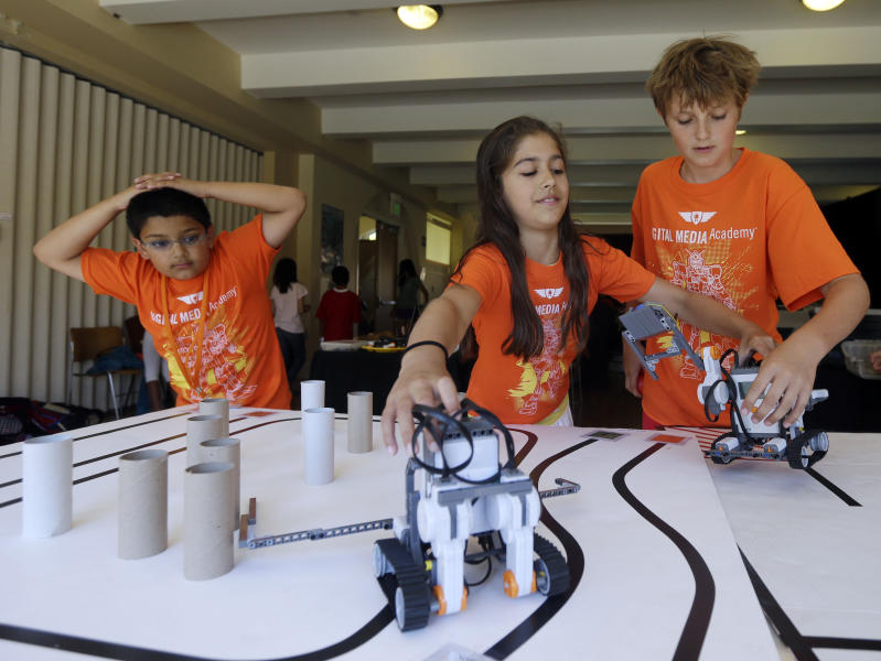 In this Aug. 14, 2013, photo, Saci Marty, 10, center, and Callum Brown, 11, at right, put their robotic Lego Mindstorms units through an obstacle course during a Digital Media Academy workshop, in Stanford, Calif. Lego's new Mindstorms sets rolling out next month are keenly anticipated by Silicon Valley engineers_many of whom were drawn to the tech sector by the flagship kits that came on the market in 1998, introducing computerized movement to the traditional snap-together toy blocks and allowing the young innovators to build their first robots. (AP Photo/Marcio Jose Sanchez)