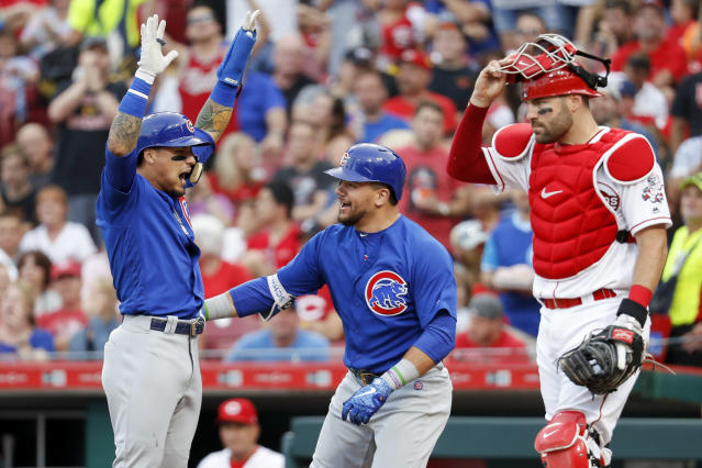 Chicago Cubs' Kyle Schwarber, center, celebrates with Javier Baez, left, after hitting a two-run home run off Cincinnati Reds starting pitcher Luis Castillo during the fourth inning of a baseball game Friday, June 22, 2018, in Cincinnati. (AP Photo/John Minchillo)