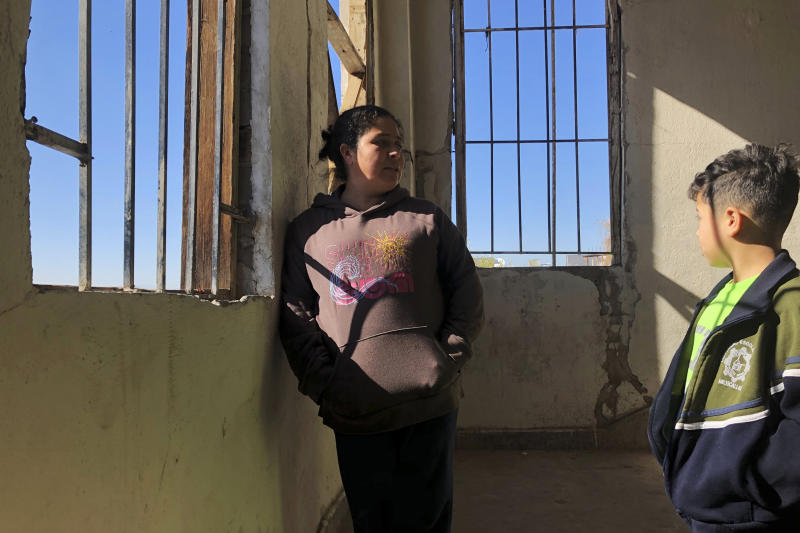In this Jan. 11, 2020, photo, Enma Floriana chats with her 13-year-old son in the stairway of a migrant shelter in Mexicali, Mexico. The Guatemalan family is seeking asylum in a San Diego immigration court. Illegal border crossings have plummeted as the Trump administration has extended a policy to make asylum seekers wait in Mexico for court hearings in the U.S. (AP Photo/Elliot Spagat)