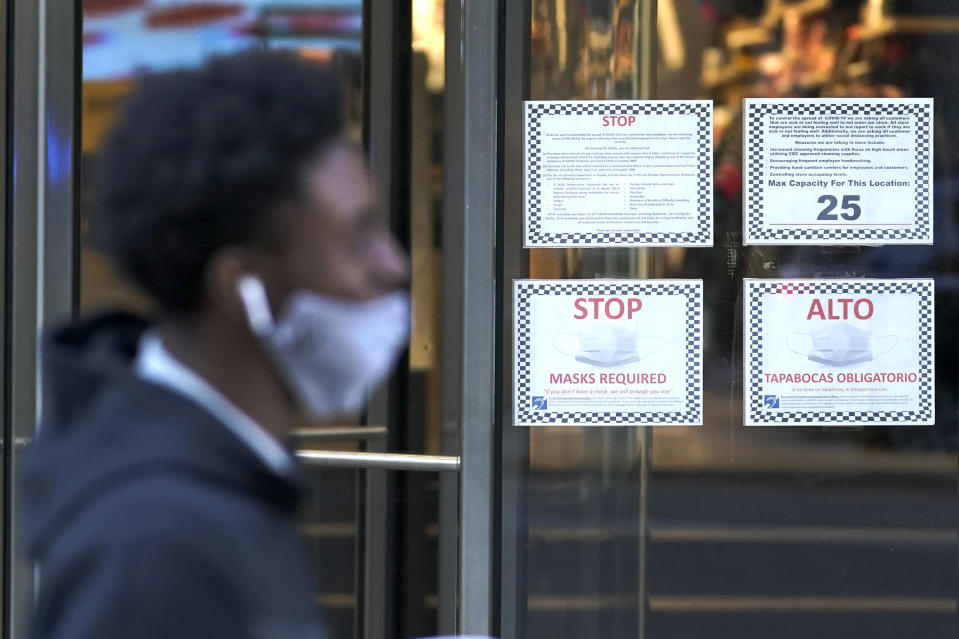 A pedestrian Wednesday, Nov. 18, 2020, walks past a bilingual COVID-19 precaution signs outside a retail store on Michigan Avenue in Chicago. The accelerating surge of coronavirus cases across the U.S. is causing an existential crisis for America's retailers and spooking their customers just as the critically important holiday shopping season nears. (AP Photo/Charles Rex Arbogast)