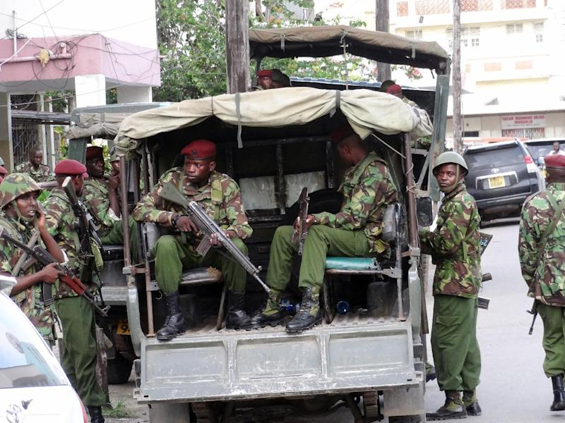 Kenya soldiers stand by as hundreds of people attend the funeral ceremony for moderate Muslim cleric Mohamed Idris, shot dead by unidentified gunmen on June 10, 2014 in the Kenyan port city of Mombasa