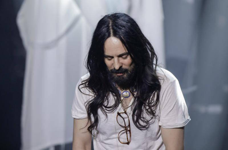 FILE - In this Wednesday, Feb. 19, 2020 file photo, Designer Alessandro Michele acknowledges the applause at the end of Gucci's Fall/Winter 2020/2021 collection, presented in Milan, Italy. Gucci and St. Laurent are two of the highest profile luxury fashion houses to announce they will leave the fashion calendar behind, with its relentless four-times-a-year rhythm, shuttling cadres of fashionistas between global capitals where they squeeze shoulder-to-shoulder around runways for 15 breathless minutes. (AP Photo/Luca Bruno, File)