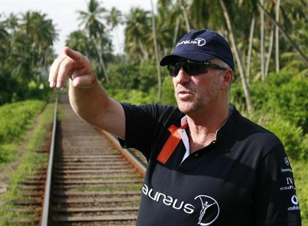 Former England cricket player Ian Botham gestures next to the train tracks as he talks about the train that was pushed off the tracks by the December 2004 tsunami, killing over a thousand people, in Paraliya, 90 km (55 miles) south of Colombo, December 1, 2009. REUTERS/Andrew Caballero-Reynolds
