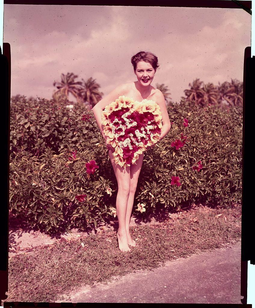 <p>Model Joyce Chrest poses with some carefully placed Hibiscus blooms. </p>