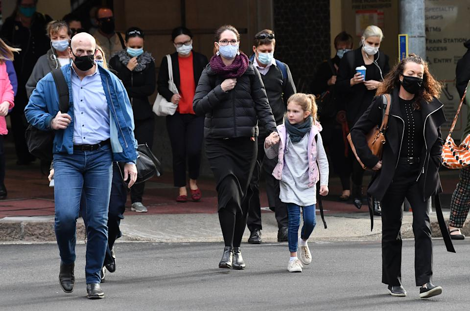 People wearing protective face masks are seen in the CBD of Brisbane. Source: AAP