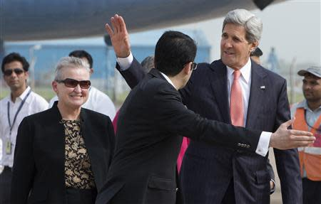 File photo of U.S. Secretary of State Kerry waving in front of U.S. Ambassador to India Nancy Powell in New Delhi