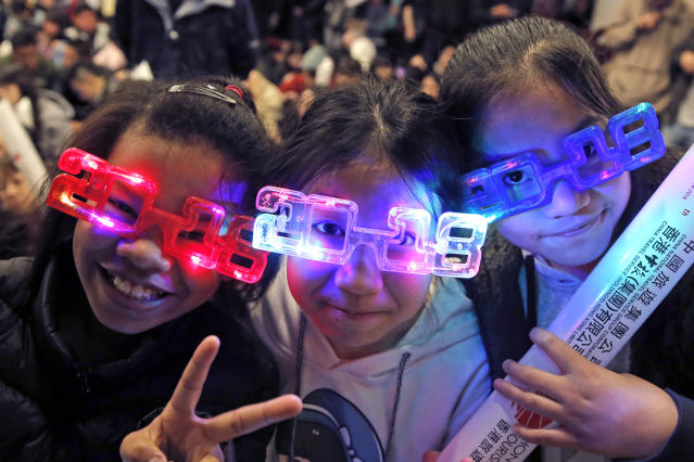<p>Residents wear 2018 glasses, during New Year's Eve to celebrate the upcoming year 2018 in Hong Kong, Sunday, Dec. 31, 2017. (Photo: Kin Cheung/AP) </p>