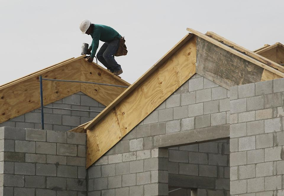 A construction worker is seen on the roof of a house under construction. (Photo: Joe Raedle/Getty Images)