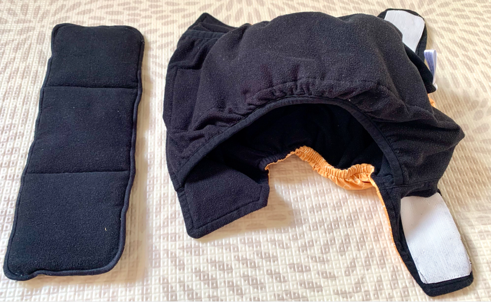 a ModiBodi cloth nappy laid out to show the open cut design, beside a booster pad
