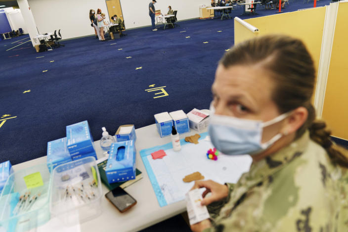 Tape on the floor marks where a line would normally form for people arriving for their COVID-19 inoculation as U.S. Air National Guard Capt. Jennifer Blake, right, waits for patients at a mass-vaccination site at the former Citizens Bank headquarters in Cranston, R.I., Thursday, June 10, 2021. The U.S. is confronted with an ever-growing surplus of COVID-19 vaccines, looming expiration dates and stubbornly lagging demand at a time when the developing world is clamoring for doses to stem a rise in infections. (AP Photo/David Goldman)