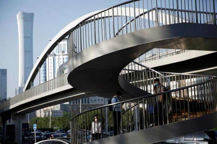 People are seen at a footbridge in Beijing's central business district