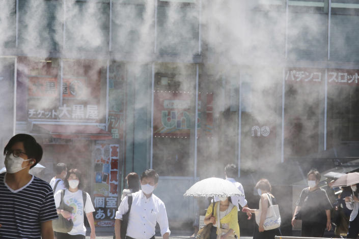 People wearing face masks to help protect against the spread of the coronavirus walk under a cooling water mist during the heat of the day in Tokyo Thursday, Aug. 5, 2021. (AP Photo/Koji Sasahara)