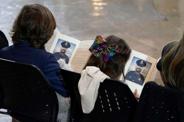 PHOTO: Logan Evans (L) and Abigail Evans, children of late U.S. Capitol Police officer William Evans, look at the program with a photo of their father as he lies in honor in the U.S. Capitol rotunda, April 13, 2021 in Washington, DC. (J. Scott Applewhite/Getty Images)